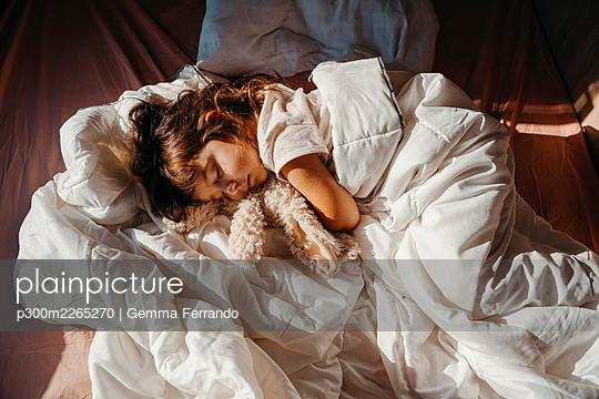 Sweet little girl sleeping in motor home with stuffed rabbit toy - p300m2265270 by Gemma Ferrando