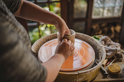 Midsection of craftsperson molding clay on pottery wheel at workshop - p1166m1512992 by Cavan Images