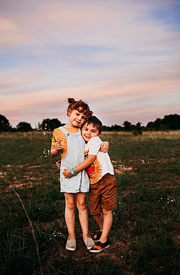 Young brother and sister standing outside hugging at sunset - p1166m2201237 by Cavan Images