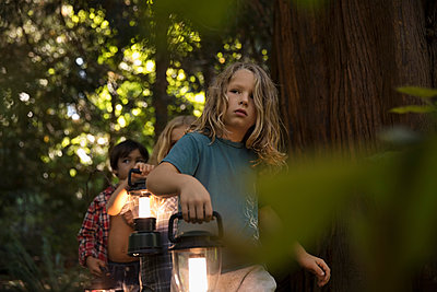 Curious boy and girl friends with lanterns exploring in woods - p1192m1511945 by Hero Images