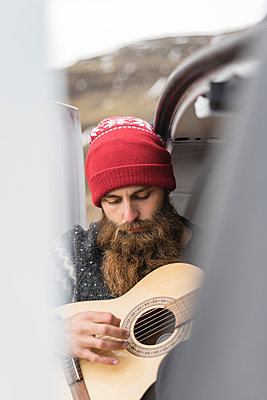 Portrait of hipster wearing red woolly hat playing guitar - p300m1588202 von VITTA GALLERY