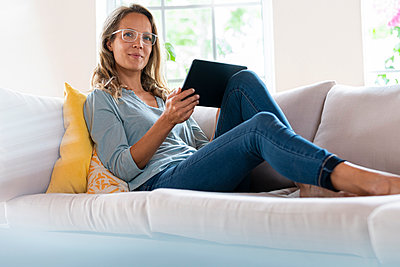 Beautiful woman with digital tablet relaxing on sofa in living room - p300m2276404 by Steve Brookland
