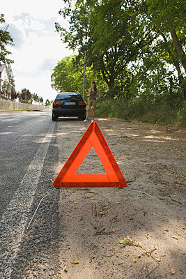 A warning triangle behind a car on the side of a road - p30118025f by Halfdark