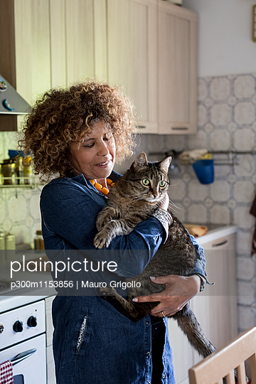 Woman cuddling with cat in kitchen - p300m1153856 by Mauro Grigollo