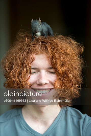 Portrait of happy redheaded teenage boy with squirrel on his head