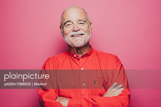 Portrait of smiling senior man with arms crossed against pink background - p426m1588532 by Maskot