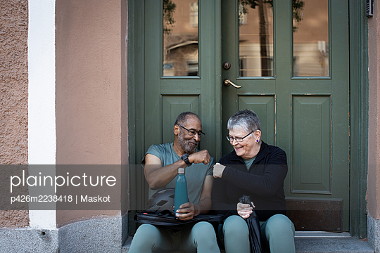 Smiling senior couple doing fist bump against doorway of house - p426m2238418 by Maskot