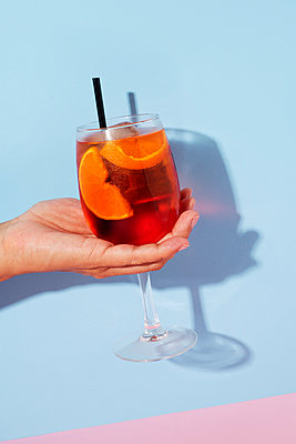 Hand with a Aperol Spritz on a blue background - p1423m2013669 by JUAN MOYANO