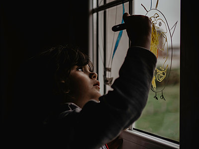 Little girl painting on window glass - p1522m2168619 by Almag