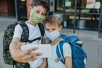 Brothers taking selfie on smart phone while wearing protective face mask standing in front of school building - p300m2226121 by Mareen Fischinger
