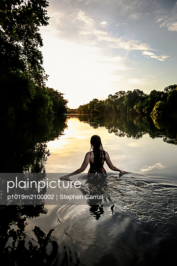 Sunset, Woman in river, rear view - p1019m2100002 by Stephen Carroll