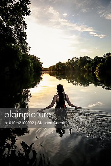 Frau bei Sonnenuntergang im Fluss, Rückansicht - p1019m2100002 von Stephen Carroll