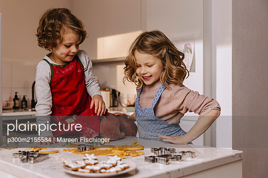 Two happy girls preparing Christmas cookies in kitchen - p300m2155584 by Mareen Fischinger