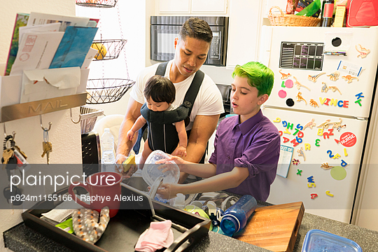 Son helping father with baby in carrier wash dishes - p924m1155166 by Raphye Alexius