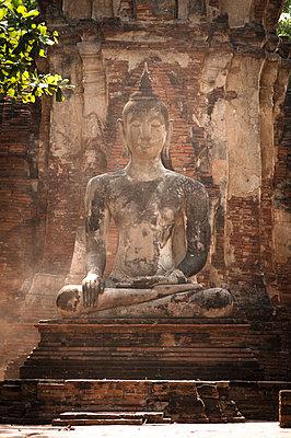 Buddha Statue vor Ziegelmauer - p1273m1496184 von melanka