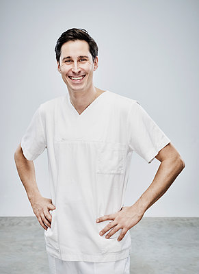 Male nurse with hands on hip - p1312m1514855 by Axel Killian