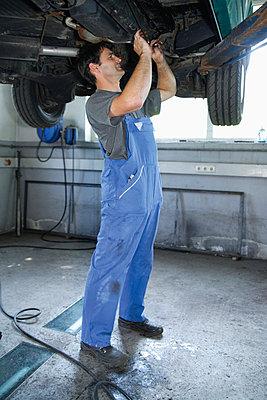 Germany, Ebenhausen, Mechatronic technician working in car garage - p30020024f by Tom Chance