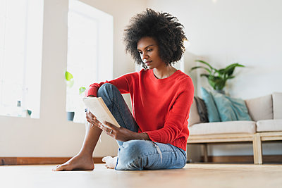 Young woman reading book while sitting in living room - p300m2277539 by Steve Brookland