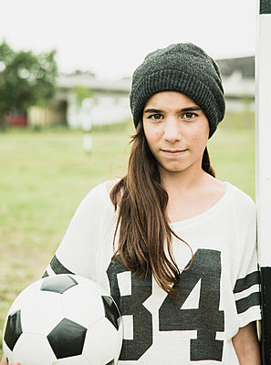 Portrait of teenage girl with soccer ball leaning at goalpost - p300m950160f by Uwe Umstätter