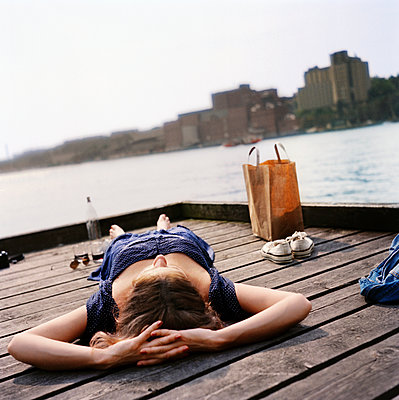 Woman lying on jetty - p312m2237226 by Pernille Tofte