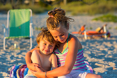 Caucasian children hugging on beach - p555m1411350 by Marc Romanelli