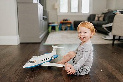 Toddler playing with toy aeroplane in living room - p924m2153064 by Sara Monika