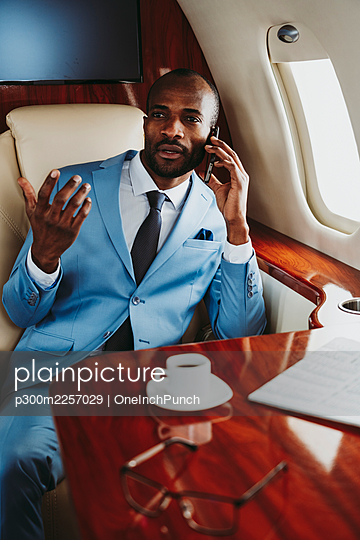 Elegant businessman talking on smart phone while traveling in airplane - p300m2257029 by OneInchPunch