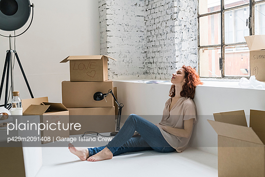 Mid adult woman sitting on floor relaxing, moving into industrial style apartment - p429m2091408 by Garage Island Crew