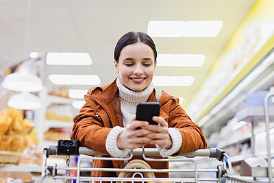 Woman with smart phone pushing shopping cart in supermarket - p1023m2187676 by Sam Edwards