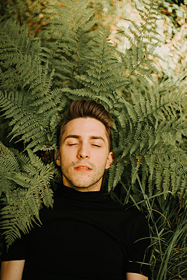 Man with closed eyes between fern leaves - p1267m2259755 by Jörg Meier