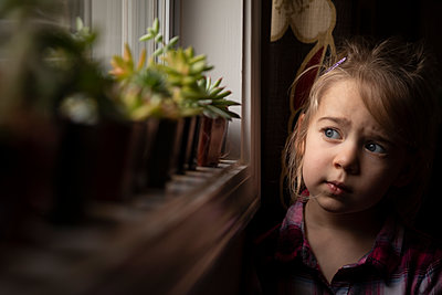 Portrait of a young girl looking out a window by succulents - p1480m2148202 by Brian W. Downs