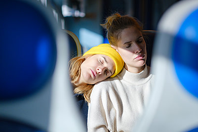 Two young women have a nap on the train - p1600m2175104 by Ole Spata