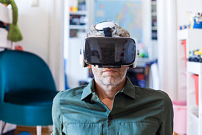 Portrait of mature man at home using Virtual Reality Glasses - p300m2030569 by Tom Chance