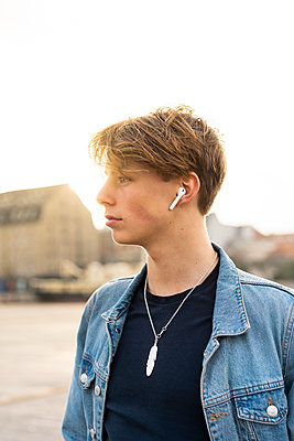 Denmark, Copenhagen, portrait of young man with earbuds in the city - p300m2102131 von VITTA GALLERY