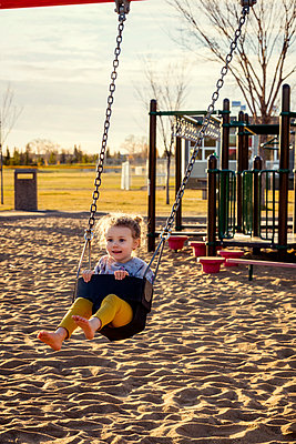 A young girl swinging by herself in a playground and enjoying a warm fall evening; Edmonton, Alberta, Canada - p442m2012179 by LJM Photo