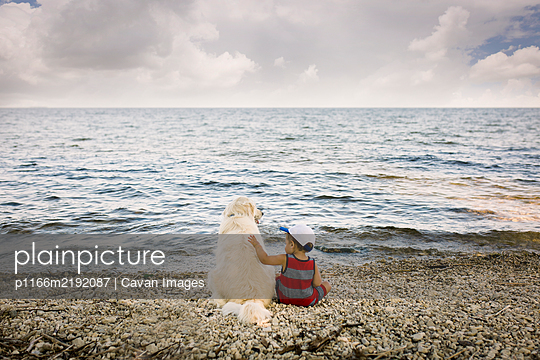 Toddler boy sitting with golden retriever dog on beach looking at lake - p1166m2192087 by Cavan Images