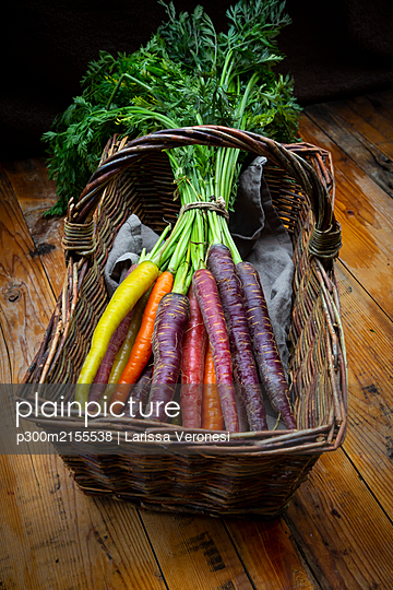 Wicker basket with bundle of fresh colorful carrots - p300m2155538 by Larissa Veronesi