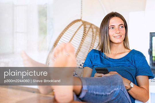 Smiling relaxed female professional looking away while sitting with smart phone and feet up at table in home office - p300m2244060 by Steve Brookland