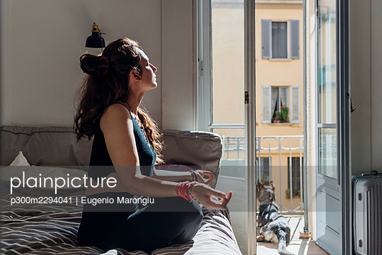 Woman meditating while practicing yoga on bed in apartment - p300m2294041 by Eugenio Marongiu