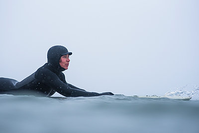 Woman surfing during winter snow - p1166m2177146 by Cavan Images