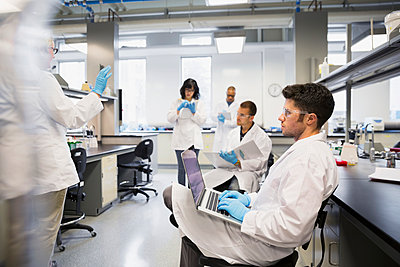Science students taking notes in laboratory - p1192m1036738f by Hero Images