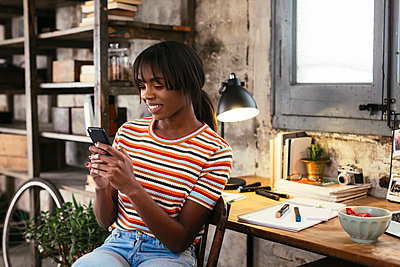 Smiling young woman sitting in front of desk in a loft looking at cell phone - p300m1581074 by Bonninstudio