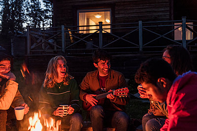 Group of friends sitting at a campfire, talking and playing guitar - p300m2042446 by Kike Arnaiz