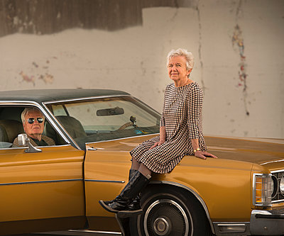 Portrait of cool senior woman sitting on bonnet of husbands classic automobile - p429m935416 by JLPH