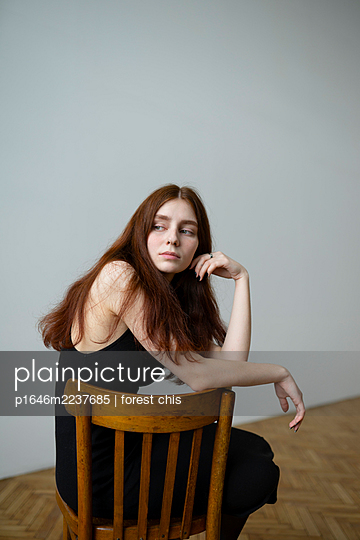 Young woman with brown hair sits on chair - p1646m2237685 by Slava Chistyakov