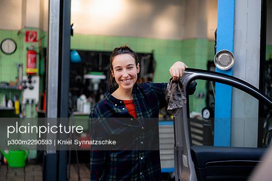 Smiling female mechanic opening car door at workshop - p300m2290593 by Kniel Synnatzschke