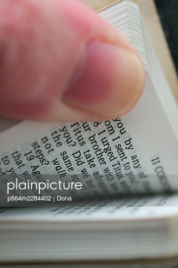 Finger thumbing through the pages of a book - p564m2284402 by Dona