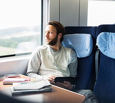 Mann hört im Zug Musik - p1114m1159788 von Carina Wendland