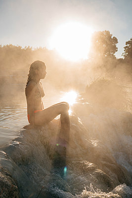 Side view of woman sitting on rocks in steam emitting thermal pool during sunny day - p1166m1554297 by Cavan Images