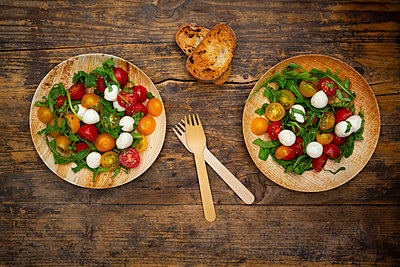 Salat mit Ruccola, Mozarella, Tomaten und Basilikum - auf umweltfreundlichem Einweggeschirr aus Palmblättern, Holzgabel - p300m2143992 von Larissa Veronesi